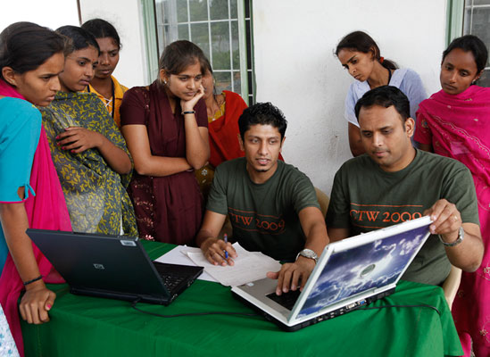 Two volunteers showing a group of women a laptop