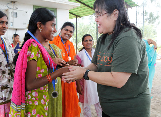 A volunteer greeting a woman in a sari