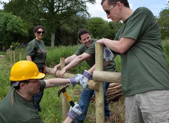 Four people repairing a wood fence