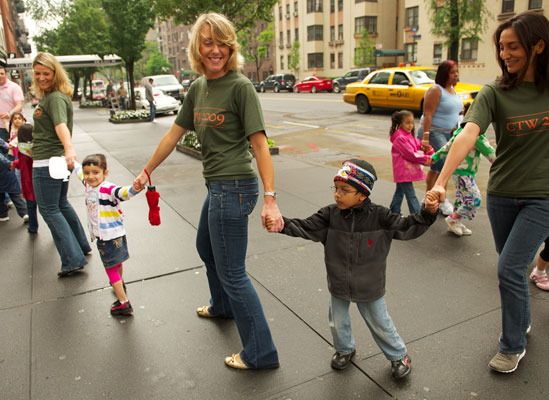 Three women walking down the street holding children's hands