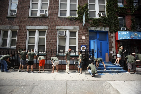 People painting a metal fence on a New York City street