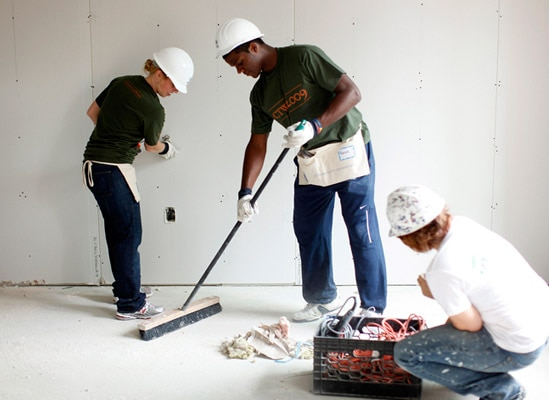 Three people in hard hats remodeling a room