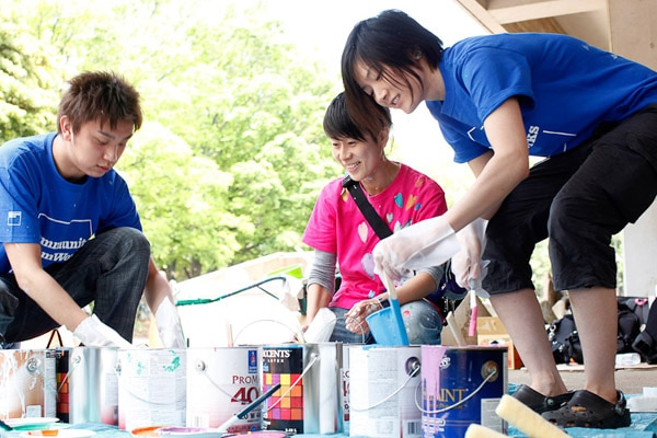Three people organizing paint buckets and paintbrushes