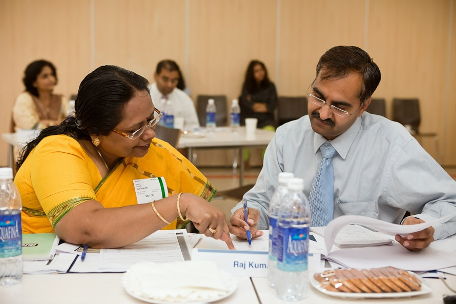 A woman and a man at a table discussing a document