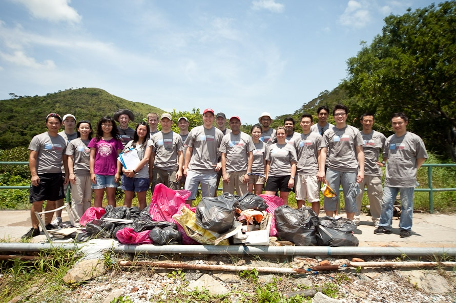 A large group of people posing with a pile of debris outdoors
