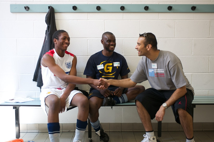 3 men sitting on a bench indoors wearing sports gear