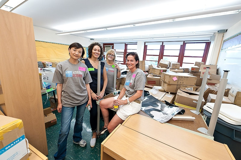 Four women volunteers posing in an cluttered classroom