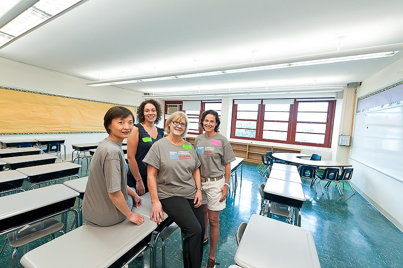 Four women volunteers posing in a very clean empty classroom