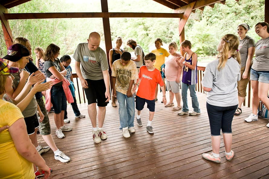 A man gives children a dance lesson as other kids and adults look on